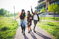 Three young female friends dancing together in park