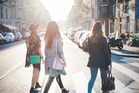 Rear view of three young women strolling over pedestrian crossing