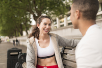 Male and female city runners relaxing on bench