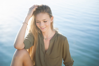Young woman sitting in front of water hand in hair looking down smiling