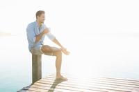 Young man sitting on lake pier drinking coffee, Woerthsee, Bavaria, Germany
