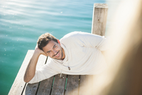 Happy young man lying on lake pier