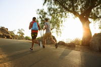 Two male friends running, outdoors, rear view