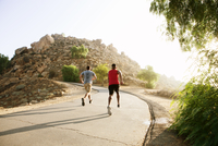 Two male friends running along mountain path,rear view