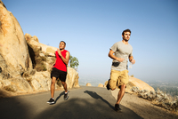 Two male friends running along mountain path