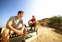 Two male friends, sitting on bench, on cliff top, looking at view