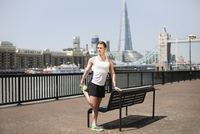 Runner stretching on riverfront, Wapping, London
