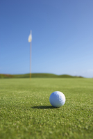 Close up of golf ball and golf flag on golf green
