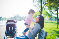 Mid adult woman with toddler daughter on park bench