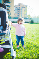 Female toddler holding onto pushchair in park
