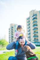 Mid adult man with toddler daughter on shoulders in park