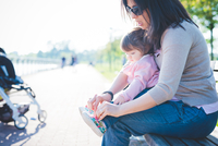 Mid adult woman tying toddler daughter shoelaces in park
