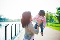 Mid adult woman lifting up toddler daughter at riverside
