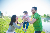 Mid adult couple handing toddler daughter to each other in park