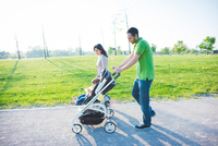 Mid adult couple and toddler daughter in pushchair strolling in park