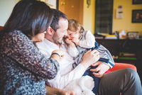 Shy female toddler sitting on fathers lap in living room