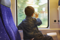 Rear view of boy with his hand against train carriage window