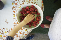 Overhead view of boys hand picking up fresh strawberry from bowl