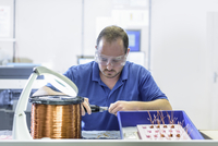 Male worker assembling electromagnetic coils in electronics factory