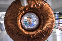 Worker inspecting electromagnetic coil seen through large coil in electromagnetics factory