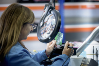 Female worker soldering electronic parts in clean room in electronics factory
