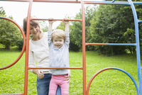 Mother and female toddler playing on park climbing frame