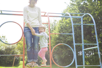 Mother and female toddler playing on climbing frame