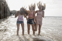 Three windswept young women having fun paddling in sea, Santa Monica, California, USA