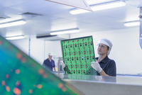 Female worker inspecting circuit boards in circuit board factory