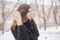 Young woman playing with her hair, wintry background