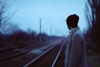 Young man looking out railway lines at dusk