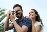 Young man with girlfriend taking photographs