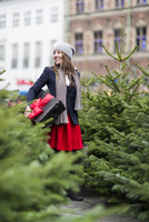 Mature woman with Christmas gift among Christmas trees