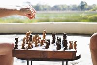 Cropped shot of woman and man playing chess at safari lodge, Kafue National Park, Zambia