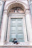 Lesbian couple sitting in oversized church doorway looking at book, Piazza Santa Maria Novella, Florence, Tuscany, Italy