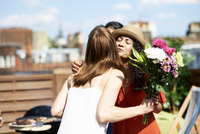 Female friends greeting with flower bouquet at rooftop barbecue 11015266908| 写真素材・ストックフォト・画像・イラスト素材|アマナイメージズ