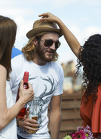 Woman putting straw hat on male friend at rooftop party