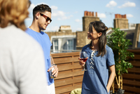 Male and female friends chatting and drinking at rooftop  party