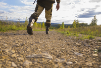 Mid adult man walking on dirt path, low section