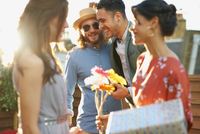 Friends at party on roof terrace holding flowers and gift smiling 11015267159| 写真素材・ストックフォト・画像・イラスト素材|アマナイメージズ