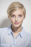 Studio portrait of young woman with blue eyes and short blond hair