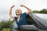 Happy young woman leaning out of open car window