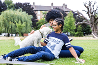 Boy and mother playing with dog in park