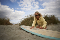 Senior woman on beach, waxing surfboard