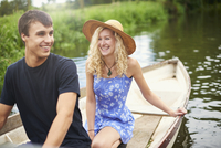 Young couple in rowing boat on rural river