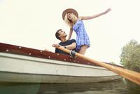 Low angle view of young woman standing in rowing boat on river