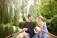 Romantic young couple in rowing boat on rural river