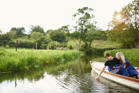 Young man with girlfriend touching water from river  rowing boat