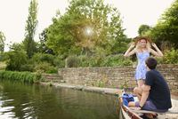 Young woman with boyfriend standing in rowing boat on river