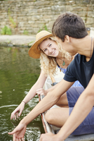 Young couple touching water from rowing boat on rural river
